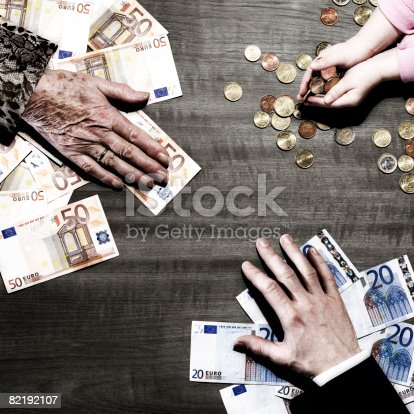 istock 3 people's hands with money on table 82192107