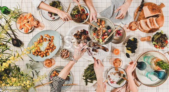 Family or friends gathering dinner. Flat-lay of peoples hands, roasted lamb shoulder, salads, vegetables, rose wine, mimosa branches over white checkered tablecloth, top view. Celebration party dinner