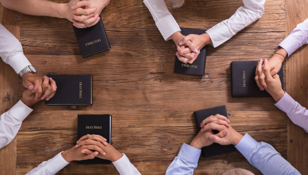 people's praying hands on holy bible - preacher stock photos and pictures