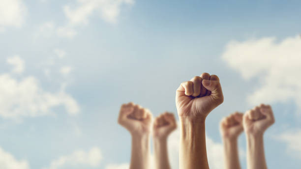 Peoples raised fist air fighting and sunlight effect, Competition, teamwork concept. Peoples raised fist air fighting and sunlight effect, Competition, teamwork concept. labor union stock pictures, royalty-free photos & images