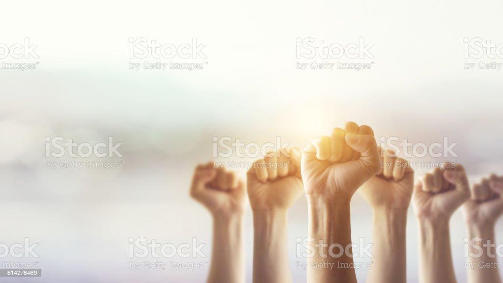 Volkeren verhoogd vuist lucht gevechten en zonlicht effect, competitie, teamwerk concept. foto