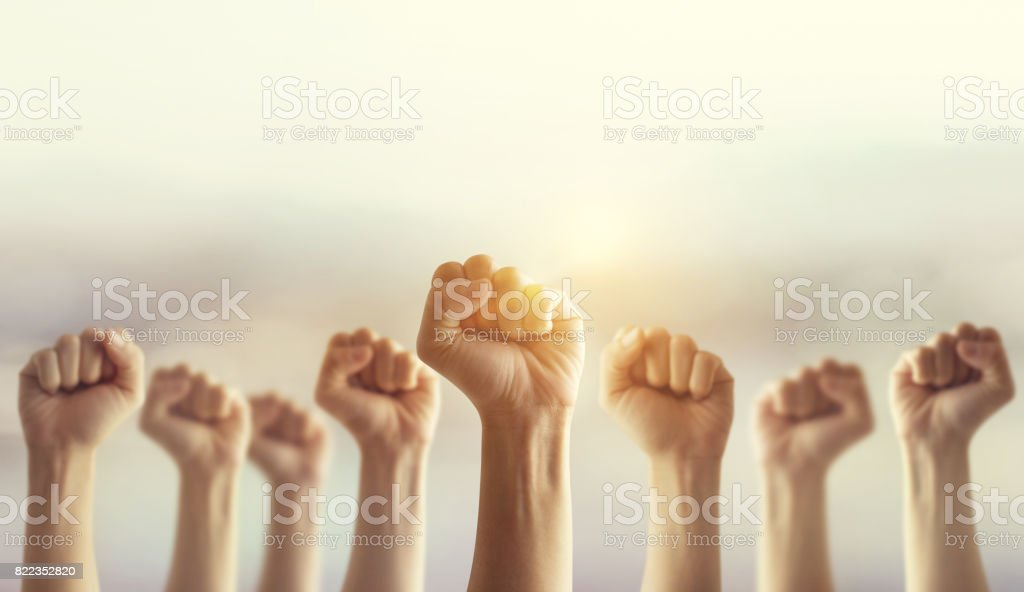 Peoples raised fist air fighting and sunlight effect, Competition, teamwork concept. stock photo
