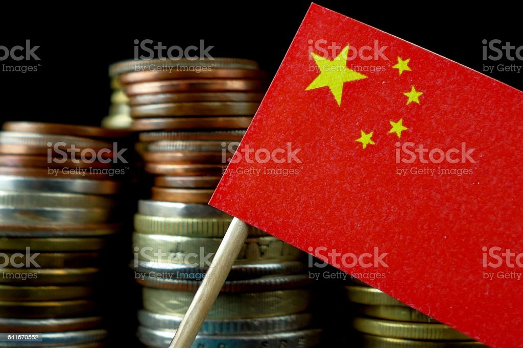 People's Republic of China flag with stack of money coins stock photo