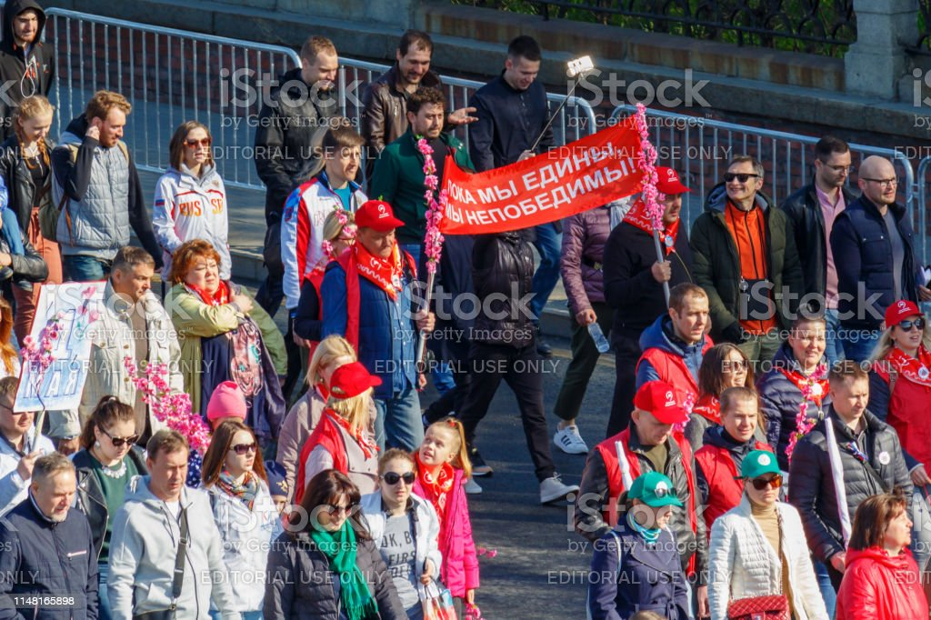 Peoples with banner and flowers on Kremlevskaya embankment go to the...
