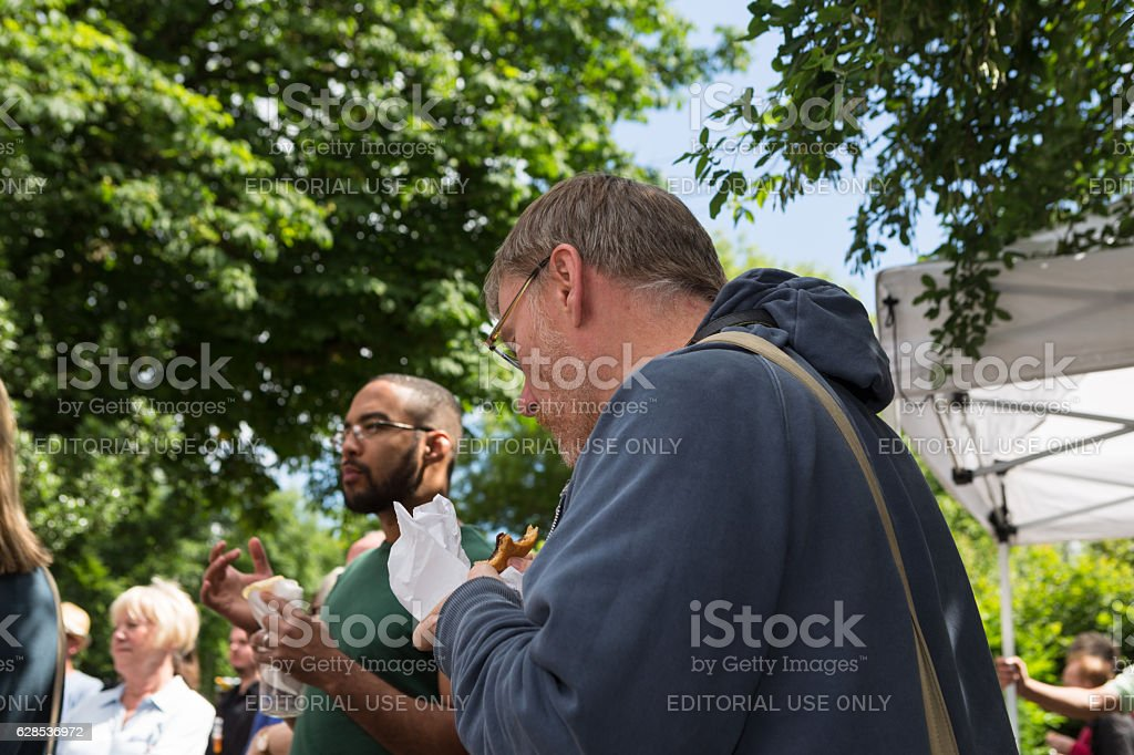 Peple eating food at an outdoor event stock photo