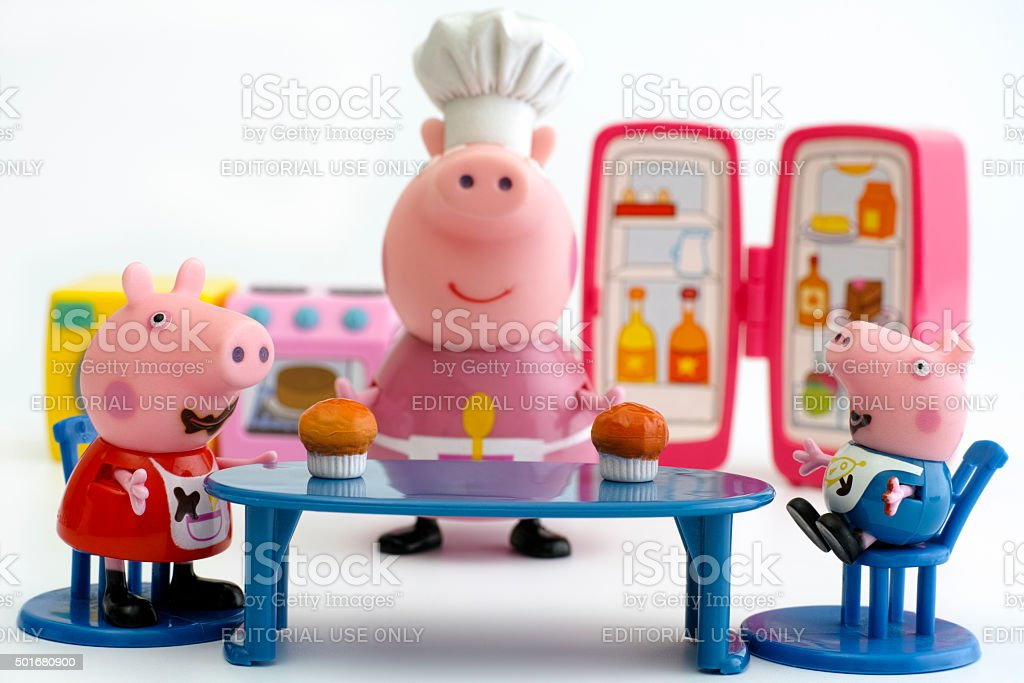 Peppa Pig and George Pig eating cupcakes stock photo