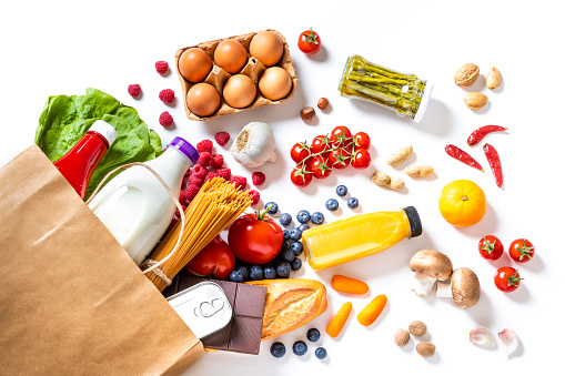 Top view of a paper bag full of canned food, fruits, vegetables, eggs, a milk bottle, berries, mushrooms, nuts, pasta, a chocolate bar and bread. The paper bag is laying on the white background and the food is coming out from it.