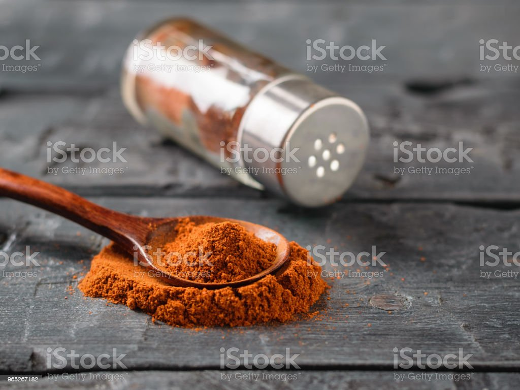 A pepper jar and a spoon of ground chili on a rustic table. royalty-free stock photo