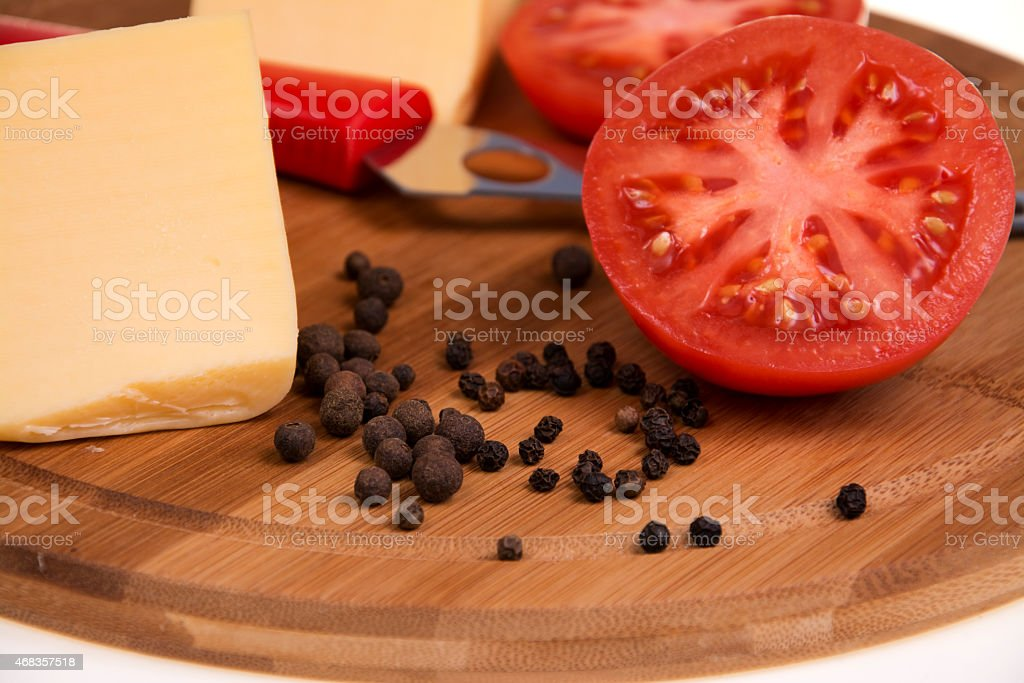 Pepper tomato and cheese on the kitchen board royalty-free stock photo