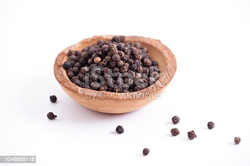 Peppercorns in wooden bowl isolated on white.