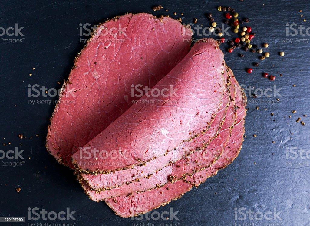 Peppered roast beef pastrami slices on paper with grains of stock photo