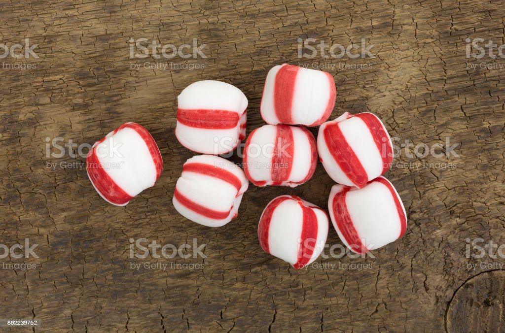 Peppermint balls on a wood board stock photo