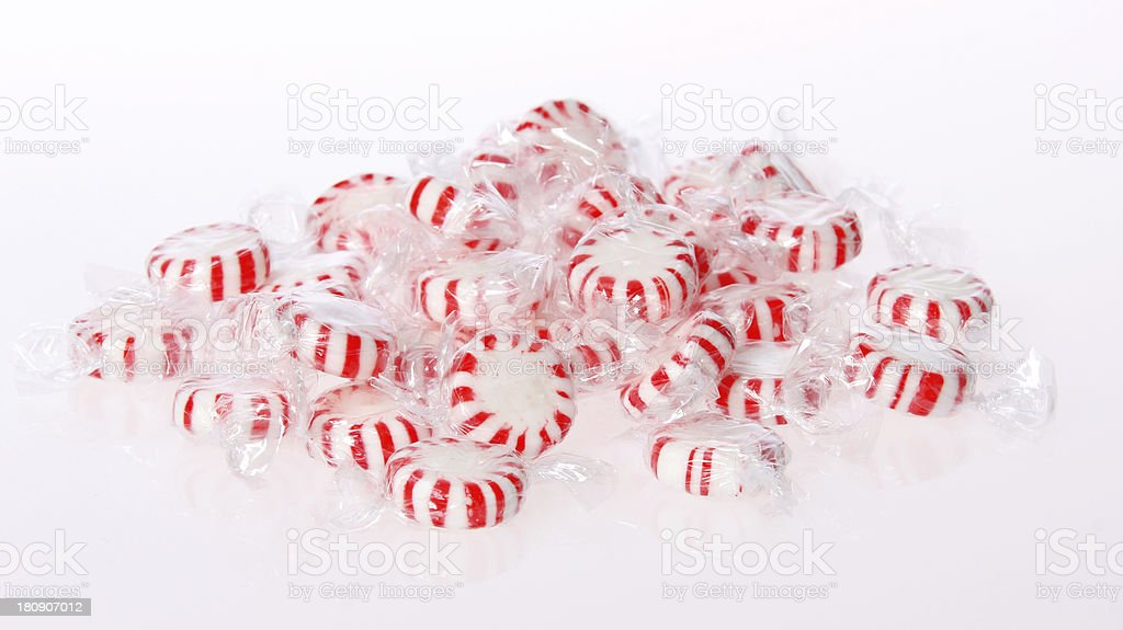 Peppermint candy pile on white background. Red striped stock photo