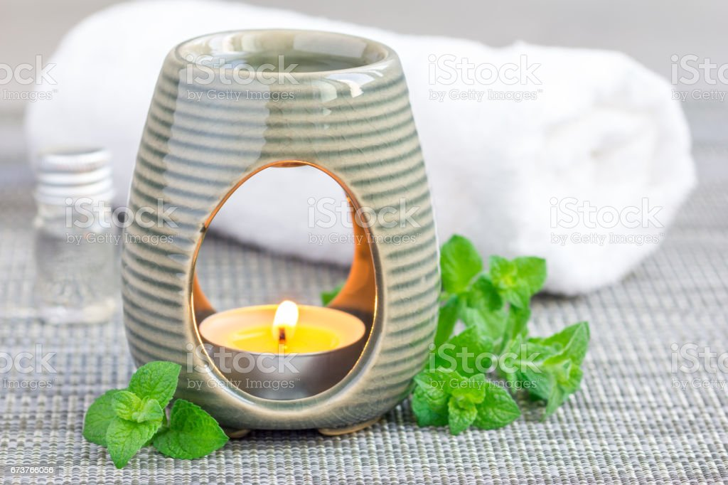 Peppermint essential oil in aroma lamp on gray mat with spa background, horizontal photo libre de droits