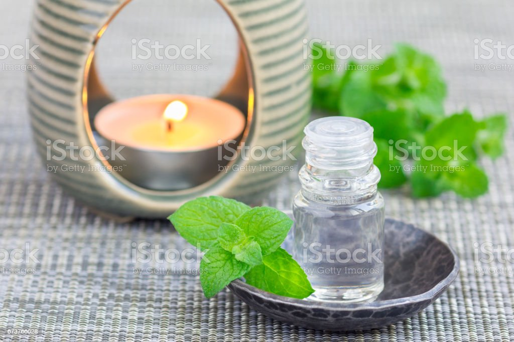 Peppermint essential oil in glass on gray mat with spa background, horizontal photo libre de droits