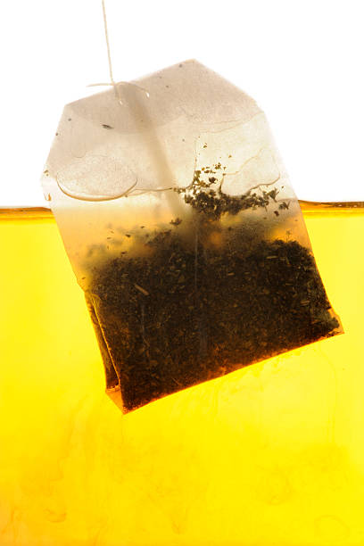 Peppermint Tea bag hanging into hot water stock photo