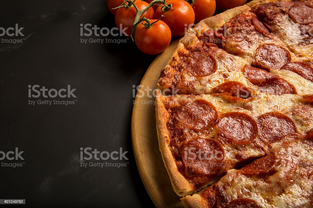 Pepperoni and cheese Pizza and tomatoes with copy area stock photo