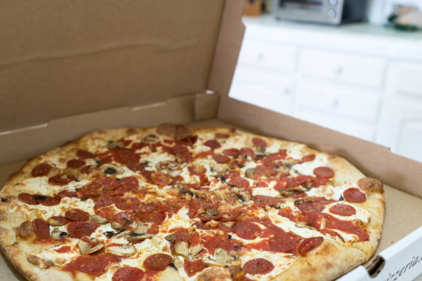 Pepperoni and Mushroom Pizza Inside Cardboard Box Side View Over Kitchen Top stock photo