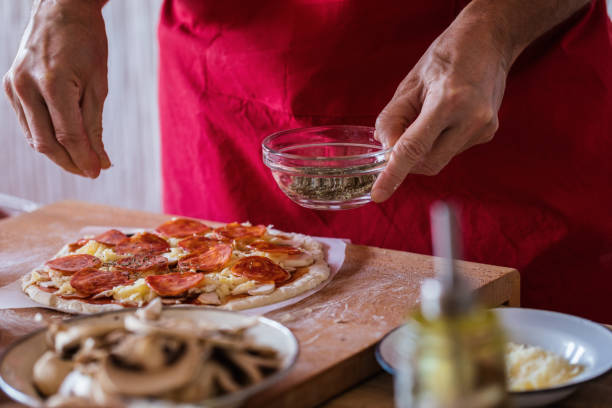 Pepperoni pizza making, dry oregano seasoning, close-up stock photo