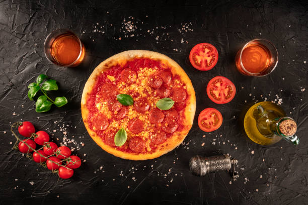 Pepperoni pizza on a black background, with wine glasses and ingredients, tomatoes, basil, and olive oil, shot from the top stock photo
