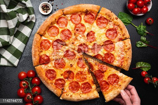 istock Pepperoni pizza on a black concrete background 1142744772