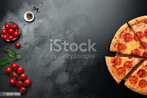 istock Pepperoni pizza on black slate background 1139597690
