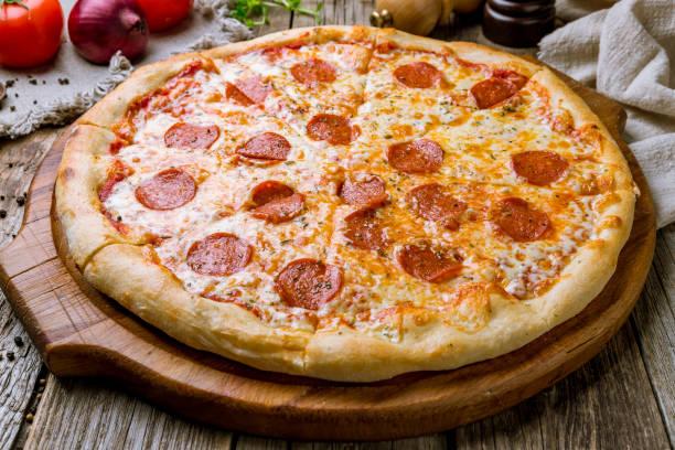 pepperoni pizza on board on wooden background - pizza стоковые фото и изображения