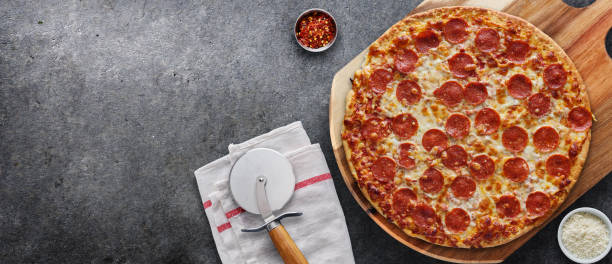 pepperoni pizza on wooden serving board stock photo