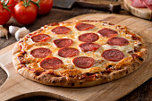 A delicious fresh homemade pepperoni pizza on a wooden pizza pull.