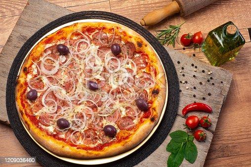 Pizza de Calabresa, com cebola fatiada , molho de tomate e azeitonas pretas, salpicada de orégano, produzida em estúdio fotográfico em cima de uma madeira rústica e diversos ingredientes para compor a cena, tais como pimenta vermelha, azeite extra virgem e manjericão