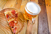 Traditional pepperoni pizza slice and beer