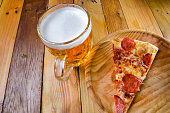 Pepperoni pizza slice and beerTraditional pepperoni pizza slice and beer