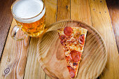 Slice of italian  pepperoni pizza and beerTraditional pepperoni pizza slice and beer