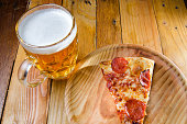 Slice of traditional  pepperoni pizza and beerTraditional pepperoni pizza slice and beer