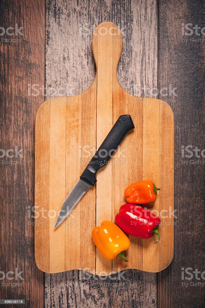 Pimenta e faca sobre uma tábua de cortar foto royalty-free