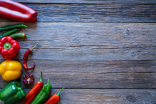 Peppers red yellow and green fresh and dried leaving wooden rustic copy space board table backgrund