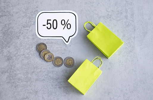 50 percent off discount promotion sale, coins and paper bags on a gray background.