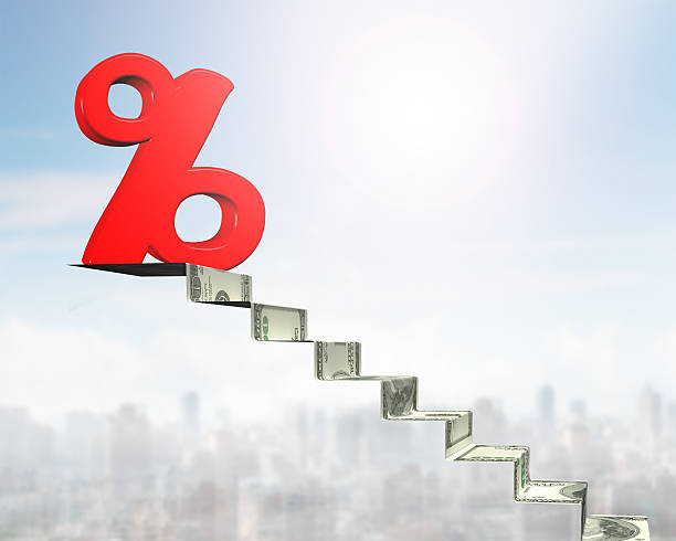 Percentage sign on top of money stairs stock photo