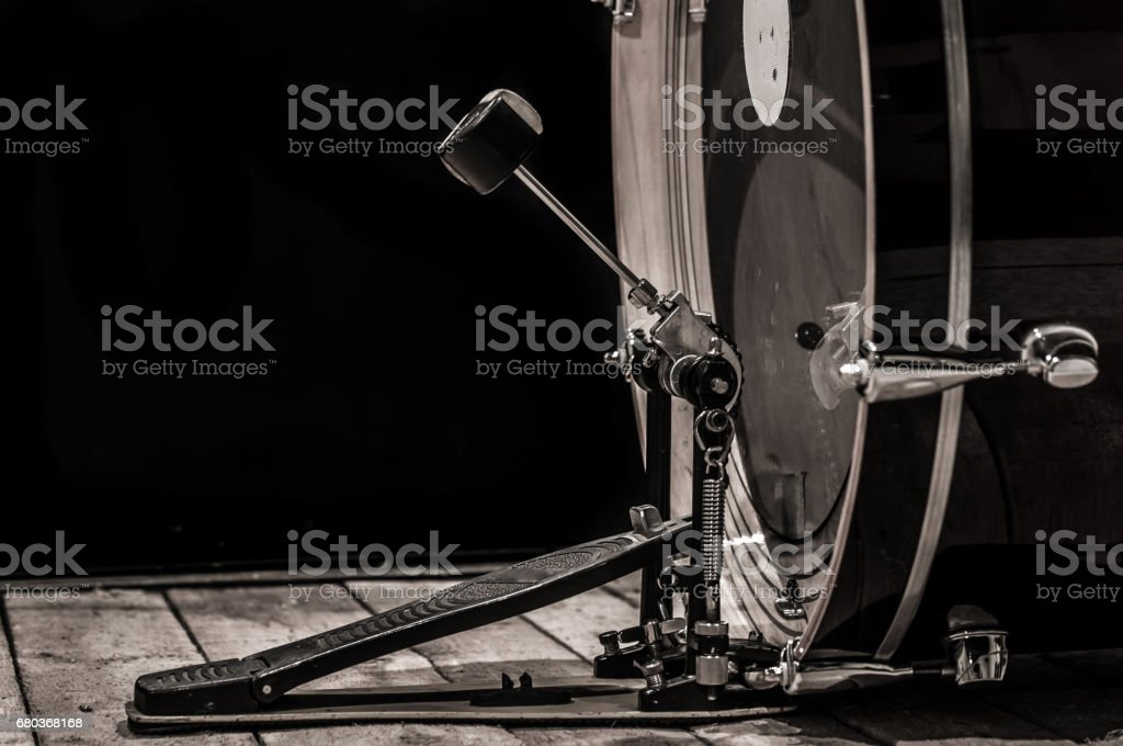 percussion instrument, bass drum with pedal on wooden boards with a black background stock photo
