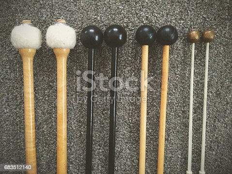 Assorted percussion mallets lined up, for playing timpani, xylophone, marimba, and glockenspiel