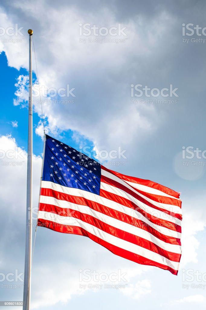 Perfect American Flag lowered to Half-Mast waving in the wind fully extended illuminated by sunshine stock photo