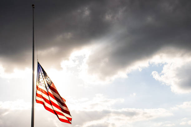 Perfect American Flag lowered to Half-Mast waving in the wind fully extended after another sad memorial stock photo
