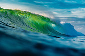 Perfect barrel wave in ocean. Breaking green wave with sun light