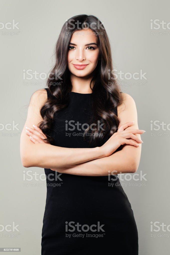 Perfecta mujer morena con pelo rizado y maquillaje. Hermosa modelo en vestido negro - foto de stock