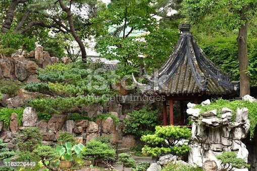 Beautiful shot of a typical traditional asian / chinese garden. Wooden pagoda with artful, ornate curved roof and red pillars, surrounded by rockery and lush green leaves, trees, plants and bushes.