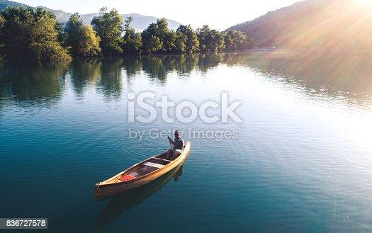 High angle shot of a man enjoying canoeing on the lake.