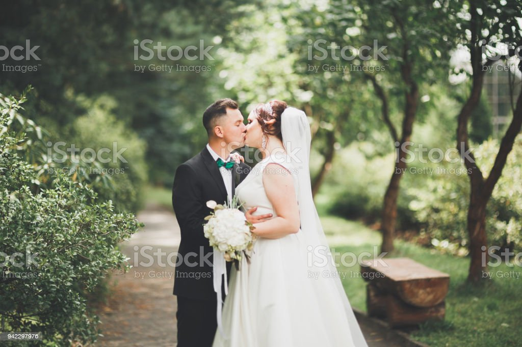 Perfect couple bride, groom posing and kissing in their wedding day stock photo