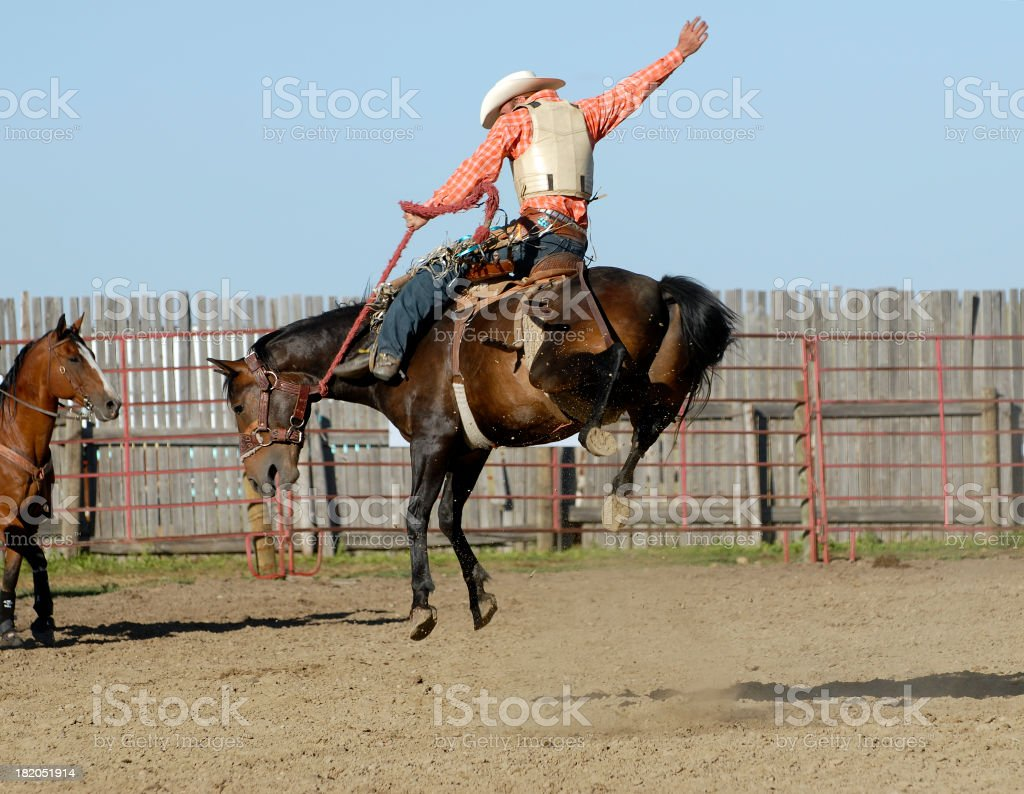 Perfect cowboy form on wild bucking horse stock photo