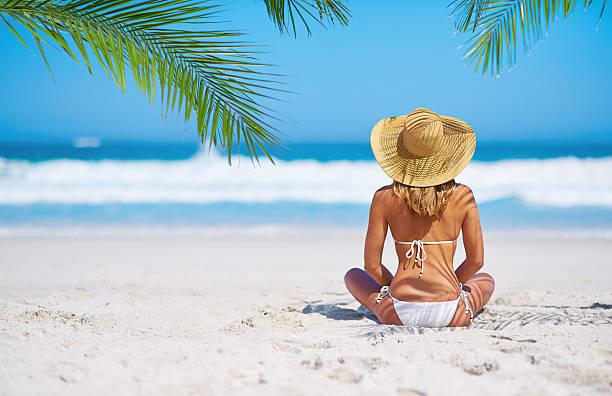 cb7f0953f55c Mujer En Traje De Baño Sentada En La Arena De La Playa - Banco de ...