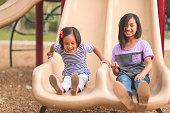 Two young sisters go down the playground slide together with big smiles